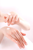 Mujer que aplica la crema en sus manos Imagen de archivo libre de regalías