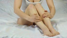 Mujer que aplica la crema en sus piernas concepto del cuidado de piel del pie, prevención de varices Cámara lenta almacen de video