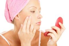Mujer que aplica la crema facial Fotos de archivo libres de regalías