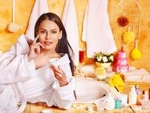 Mujer que aplica la crema hidratante. Foto de archivo