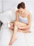 Mujer que aplica la crema para la piel en las piernas Fotos de archivo libres de regalías