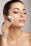 Mujer que aplica la esponja cosmética en su cara Fotos de archivo