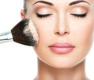 Mujer que aplica la fundación tonal cosmética seca en la cara Fotos de archivo libres de regalías
