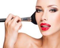 Mujer que aplica la fundación tonal cosmética seca en la cara Imagen de archivo