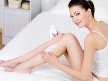 Mujer que aplica la loción de la carrocería en sus piernas Imagen de archivo libre de regalías