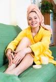 Mujer que aplica la loción de la piel a las piernas imagen de archivo libre de regalías