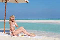Mujer que aplica la loción de Sun el día de fiesta de la playa Fotografía de archivo