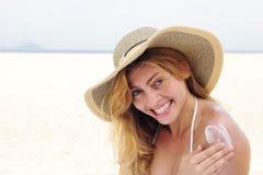 Mujer que aplica la loción del bronceado en la playa Imagenes de archivo