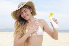 Mujer que aplica la loción del bronceado en la playa Fotografía de archivo libre de regalías