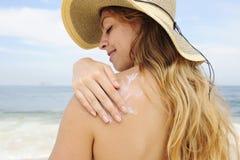 Mujer que aplica la loción del bronceado en la playa Fotografía de archivo