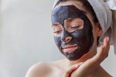 Mujer que aplica la máscara en cara Imagen de archivo