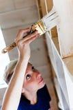 Mujer que aplica la primera capa de pintura en una biblioteca de madera foto de archivo libre de regalías