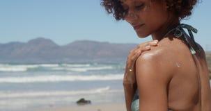 Mujer que aplica la protección solar en hombros en la playa en la sol 4k almacen de metraje de vídeo