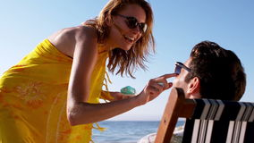 Mujer que aplica la protección solar en la nariz de un hombre almacen de video