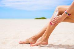Mujer que aplica la protección solar en sus piernas foto de archivo