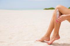 Mujer que aplica la protección solar en sus piernas fotos de archivo libres de regalías