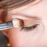 Mujer que aplica la sombra de ojos a su párpado Fotos de archivo libres de regalías