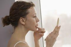 Mujer que aplica Lipgloss por la ventana fotos de archivo