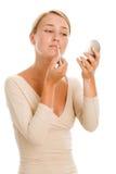 Mujer que aplica lustre del labio Fotos de archivo