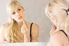 Mujer que aplica lustre del labio Foto de archivo libre de regalías