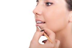 Mujer que aplica lustre del labio con el cepillo fotografía de archivo