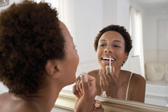 Mujer que aplica lustre del labio en espejo en casa Imágenes de archivo libres de regalías