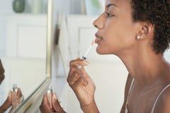 Mujer que aplica lustre del labio en espejo en casa Imagen de archivo
