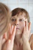 Mujer que aplica maquillaje Imagen de archivo
