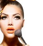 Mujer que aplica maquillaje foto de archivo