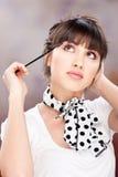 Mujer que aplica maquillaje en la pestaña Foto de archivo