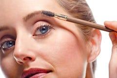 Mujer que aplica maquillaje usando cepillo de la ceja Foto de archivo