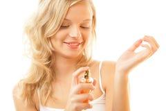 Mujer que aplica perfume en la muñeca Foto de archivo libre de regalías