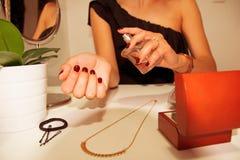 Mujer que aplica perfume en su muñeca Imágenes de archivo libres de regalías