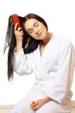 Mujer que aplica su pelo con brocha Imagenes de archivo