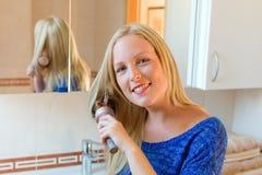 Mujer que aplica su pelo con brocha Fotografía de archivo libre de regalías