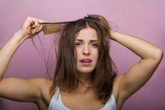 Mujer que aplica su pelo con brocha Foto de archivo