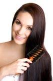 Mujer que aplica su pelo con brocha largo Foto de archivo