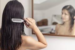Mujer que aplica su pelo con brocha mojado Fotos de archivo libres de regalías