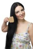 Mujer que aplica su pelo con brocha negro largo Foto de archivo libre de regalías