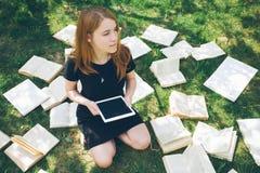 Mujer que aprende con el lector y el libro del ebook Opción entre la tecnología educativa moderna y el método tradicional de la m Fotografía de archivo libre de regalías