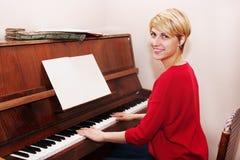 Mujer que aprende jugar el piano Imagen de archivo
