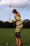Mujer que aprende jugar a golf Foto de archivo libre de regalías
