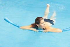 Mujer que aprende la natación con nadada Imagen de archivo libre de regalías