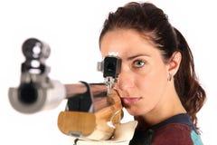 Mujer que apunta un rifle de aire neumático imagen de archivo libre de regalías