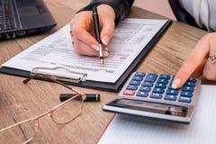 Mujer que archiva la forma individual 1040 del impuesto sobre la renta, con la calculadora imagen de archivo