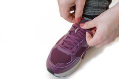 mujer que ata cordones en las zapatillas deportivas aisladas en blanco imagen de archivo