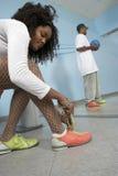 Mujer que ata el cordón de zapato Foto de archivo