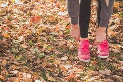 Mujer que ata el cordón en las zapatillas de deporte antes de entrenar imágenes de archivo libres de regalías