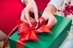 Mujer que ata la cinta en la caja de regalo Imágenes de archivo libres de regalías