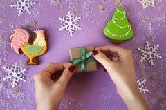 Mujer que ata la cinta verde en la caja de la Navidad Imagenes de archivo